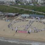 Ruim 400 yogi's vormen een vredesteken op het strand